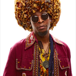 A strikingly handsome man wearing vintage clothing with a donut on his head in the shape of an afro